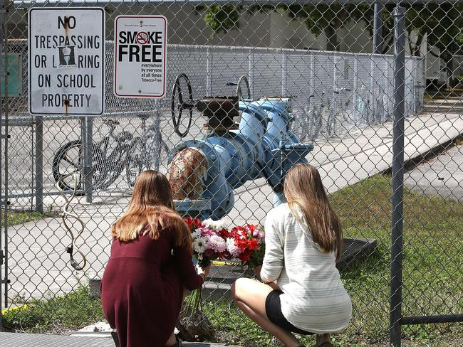 Students Jessica Garagro (l) and Sarah Goodchild, place flowers at a fence that surrounds Marjory Stoneman Douglas High School. Picture: AFP