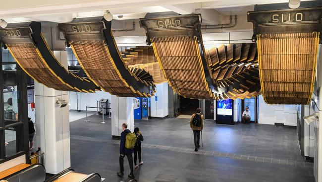 "Commuters walk under an installation by artist Chris Fox, titled ""Interloop"", a physical reinterpretation of the historic wooden-stepped escalators from Wynyard station. Picture: AAP Image/Brendan Esposito."