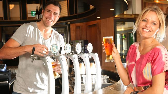 Matthew Richardson pours beers with Zoe Badwi ahead of the F1 GP at Albert Park. Picture: Herald Sun