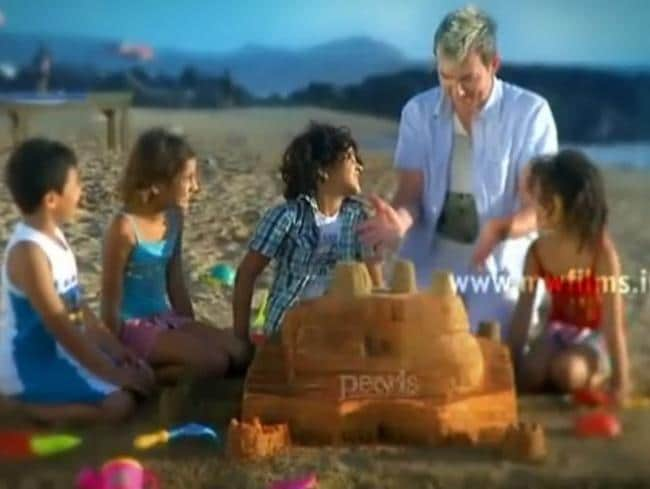 Lee builds sandcastles with children in the Pearls advertisement. Picture: YouTube.