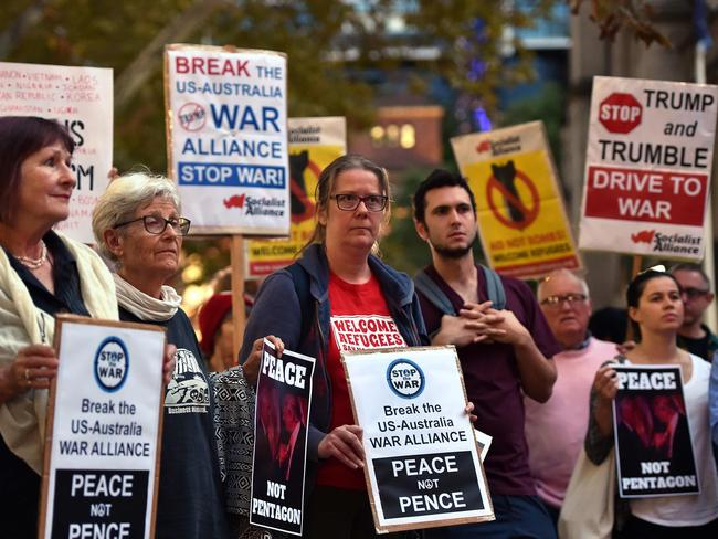 Protesters hold placards during a protest against the visit of US Vice President Mike Pence in Sydney.