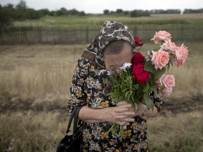 Grief ... A woman cries during a religious service held by villagers in memory of the victims at the crash site near the village of Hrabove, eastern Ukraine. Picture: AP