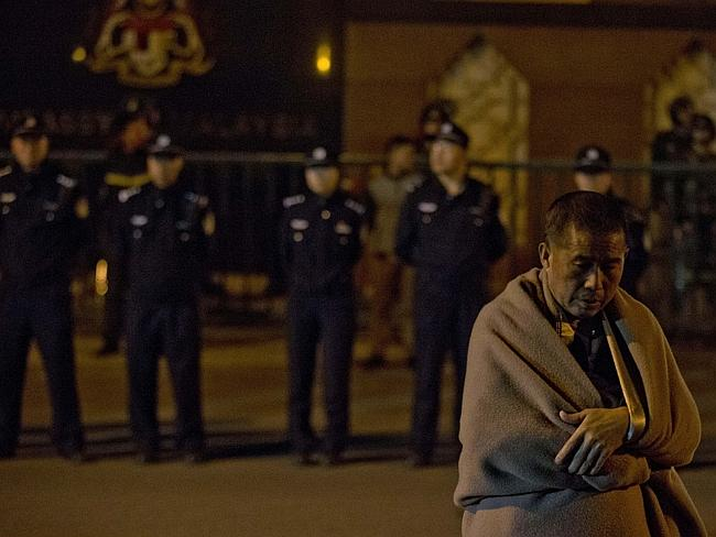 No answers ... A relative of the missing passengers waits for Malaysia embassy staff to meet their demands outside the Malaysia embassy in Beijing, China. Picture: AP