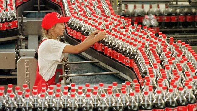 A worker checks bottles at a production line in Germany.