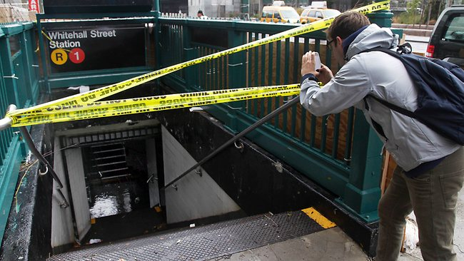A man uses his mobile phone to photograph a closed and flooded subway station in lower Manhattan, in New York. Picture: Richard Drew