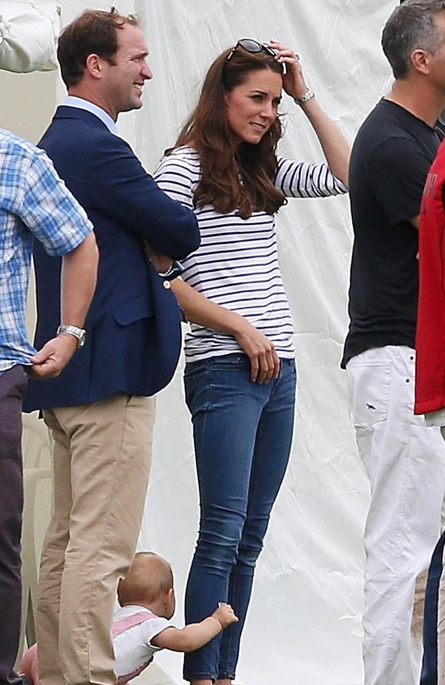 Playing at mum's feet. Catherine, Duchess of Cambridge and Prince George relax during the Royal Charity Polo.