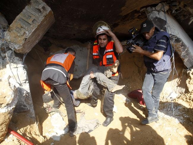 A televised war ... a journalist films as rescue workers remove the body of a Palestinian man from the rubble of his home. Picture: Said Khatib / AFP PHOTO