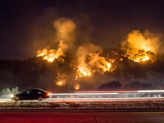 A car drives along an LA freeway as the fires burn. Picture: AFP/Kyle Grillot