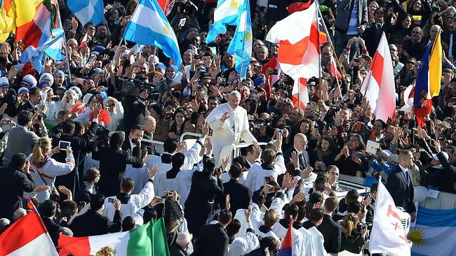 "Pope Francis waves as he arrives in the papamobile on St Peter's square for his grandiose inauguration mass on March 19, 2013 at the Vatican. The pope waved to the tens of thousands of pilgrims, who carried flags from around the world and shouted ""Long live the pope!"". AFP PHOTO / ALBERTO PIZZOLI"