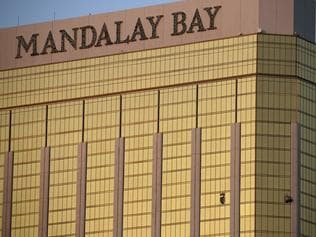 FILE - In this Monday, Oct. 2, 2017 file photo, drapes billow out of broken windows at the Mandalay Bay resort and casino on the Las Vegas Strip, following a deadly shooting at a music festival in Las Vegas. Two hotel employees had called for help and reported that gunman Stephen Paddock sprayed a hallway with bullets, striking an unarmed security guard in the leg, several minutes before Paddock opened fire from the resort on a crowd below at a musical performance, killing dozens of people and injuring hundreds. (AP Photo/John Locher, File)