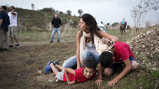 An Israeli woman and her children take cover as sirens wail in Tel Aviv.
