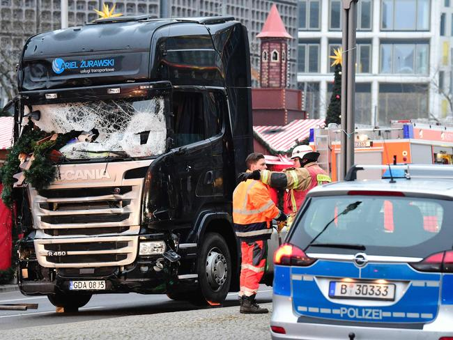 """A police car stands on December 20, 2016 in front of a truck at the site where it crashed into a Christmas market near the Kaiser-Wilhelm-Gedaechtniskirche (Kaiser Wilhelm Memorial Church) in Berlin. German police said they were treating as """"a probable terrorist attack"""" the killing of 12 people when the speeding lorry cut a bloody swath through the packed Berlin Christmas market. / AFP PHOTO / Tobias SCHWARZ"""