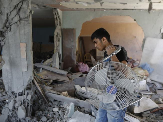 Salvage operation ... Palestinians collect belongings from a damaged building. Picture: Mohammed Abed