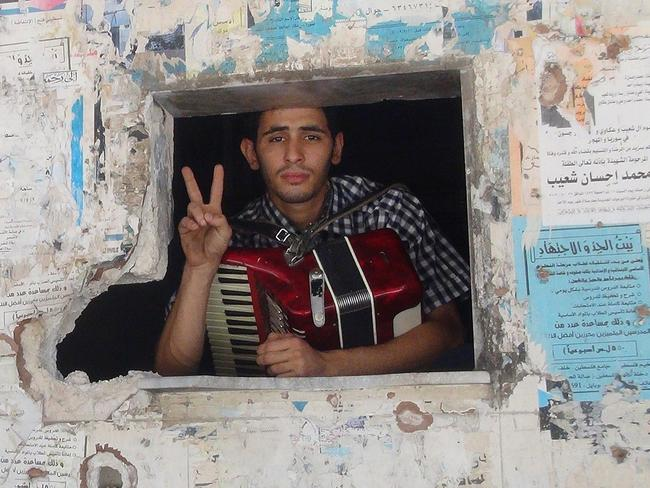 A resident of Damascus's Yarmuk Palestinian refugee camp, poses with his accordion in June.