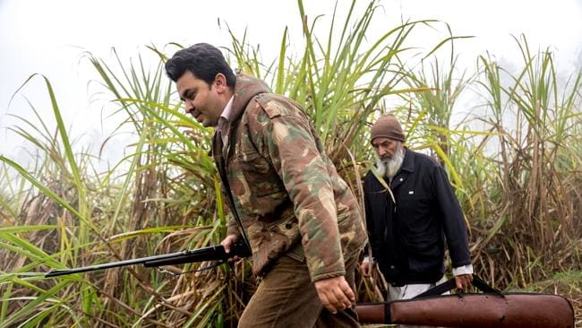 Man-eater...Sharpshooter Ali Adnan and his bearer Wajid Ali track through sugar cane fields looking for the tiger that has killed nine people. Officials say once a tiger has a taste for human flesh, the only choice is to kill it. Picture: AFP