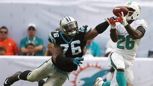 Miami Dolphins running back Lamar Miller (26) grabs a pass as Carolina Panthers defensive end Greg Hardy (76) applies pressure.