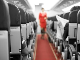 Air Travel with seats and cabin crew in background - Inside the plane