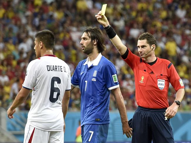 Referee Benjamin Williams, of Australia, right, gives Costa Rica's Oscar Duarte a yellow card.