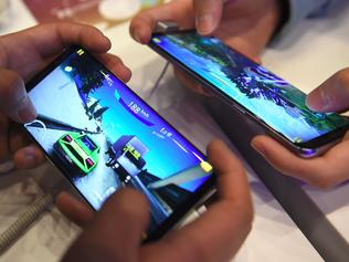 South Korean students play mobile games on Samsung Galaxy S8 smartphones at the company's showroom in Seoul on April 27, 2017. South Korean tech giant Samsung Electronics posted its biggest quarterly net profit for more than three years on April 27 after shrugging off the fallout from the exploding Galaxy Note 7 battery debacle. / AFP PHOTO / JUNG Yeon-Je