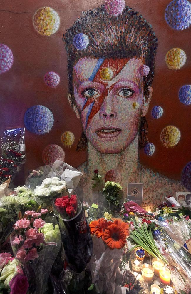 Floral tributes ... lie beneath a mural of David Bowie in London which was painted by Australian street artist James Cochran, aka Jimmy C. Picture: AFP