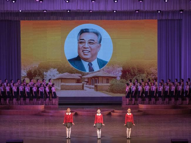 Children stand before an image of late North Korean leader Kim Il-Sung. Picture: AFP