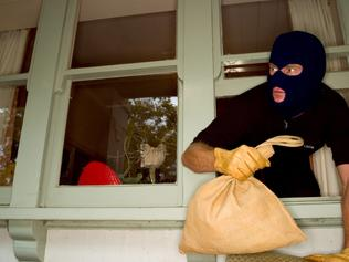 A stock Photograph of a burglar robbing a house wearing a balaclava. Thinkstock