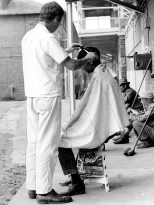 An inmate cuts another inmate's hair in Long Bay