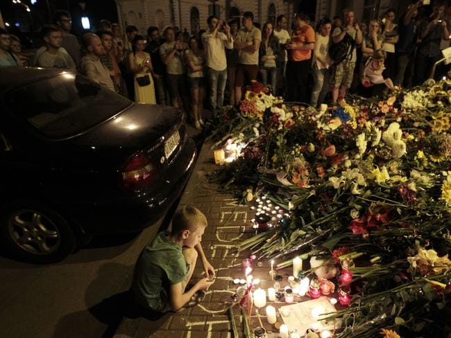 A young boy helps lay flower tributes near the Dutch embassy to express condolences to air crash victims. Picture: AP