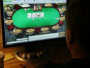 A man plays poker on his computer connected to an internet gaming site from his home in Manassas, VA 02 October, 2006. US President George W. Bush this week is expected to sign a bill making it harder to place bets on the Internet, a practice which already is illegal in the United States. Bush was expected to act quickly after Congress approved the Unlawful Internet Gambling Enforcement Act, making it illegal for financial institutions and credit card companies to process payments to settle Internet bets. It also created stiff penalties for online wagers. Billions of dollars are wagered online each year and the United States is considered the biggest market. AFP PHOTO/Karen BLEIER
