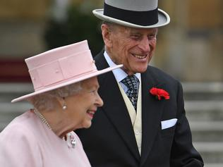 Britain's Queen Elizabeth II (L) and Britain's Prince Philip, Duke of Edinburgh (R) greet guests at a garden party at Buckingham Palace in London on May 16, 2017. / AFP PHOTO / POOL / Victoria Jones
