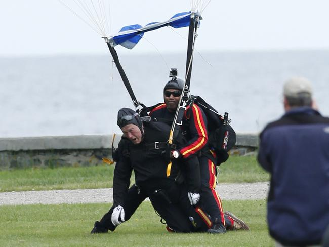 Safe landing ... George HW Bush, left, strapped to Sgt. 1st Class Mike Elliott, a retired member of the US Army's Golden Knights parachute team, land on the lawn at St. Anne's Episcopal Church in Maine.