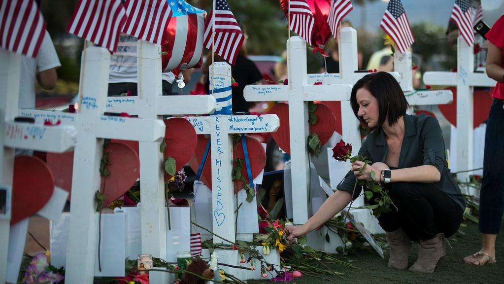 Antoinette Cannon, who worked as a trauma nurse and treated victims last Sunday night, leaves a rose at each of the 58 white crosses at a makeshift memorial on the south end of the Las Vegas Strip. Picture: AFP