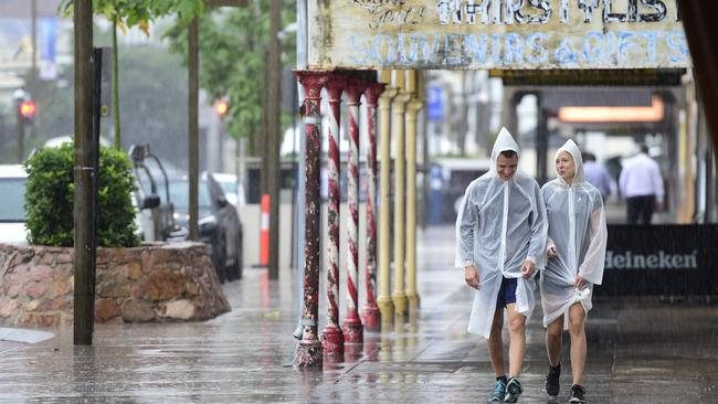 Pedro Jose Menendez and Krystle Jorja shelter from the rain while they walk down Flinders Street in Townsville. Picture: Wesley Monts