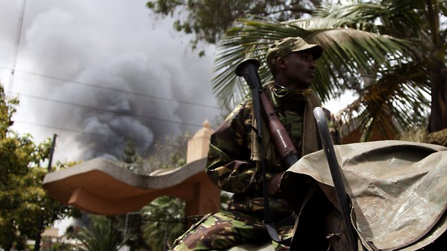 A soldier holds an RPG near the Westgate shopping mall in Nairobi, Kenya, as smoke rises from it.