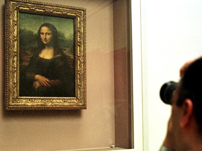 A man photographs the world's most famous painting, the Mona Lisa, which sits behind glass in temperature controlled box in the Louvre, Paris. Picture: AP.