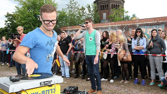 """A contestant competes in the """"Vinyl Record Spinning Contest,"""" in which competitors must run around a record player while keeping a finger on a record."""