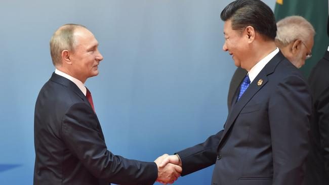 Chinese President Xi Jinping and Russian President Vladimir Putin shake hands before the Dialogue of Emerging Market and Developing Countries 2017. Picture: AFP Photo/Kenzaburo Fukuhara