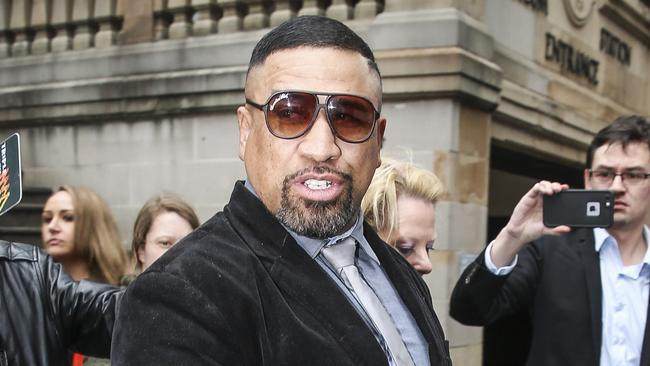 Former NRL bad boy John Hopoate has spent the night in police custody after being charged with threatening a shop owner on Sydney's north shore.