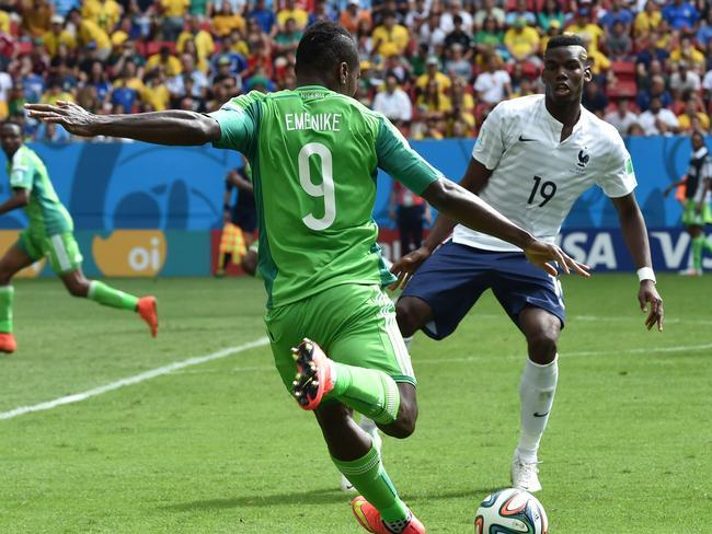 Nigeria's forward Emmanuel Emenike confronts French midfielder Paul Pogba.