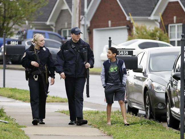 Nashville police officers talk to a boy as they search for the Waffle House restaurant shooter. Picture: AP