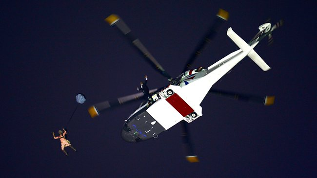 A performer in the role of Queen Elizabeth II and James Bond parachute out of a helicopter hovering above the stadium during the Opening Ceremony.
