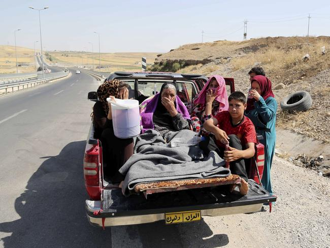Displaced ... Iraqis ride on a truck on a mountain road near the Turkish-Iraq border. Picture: Khalid Mohammed