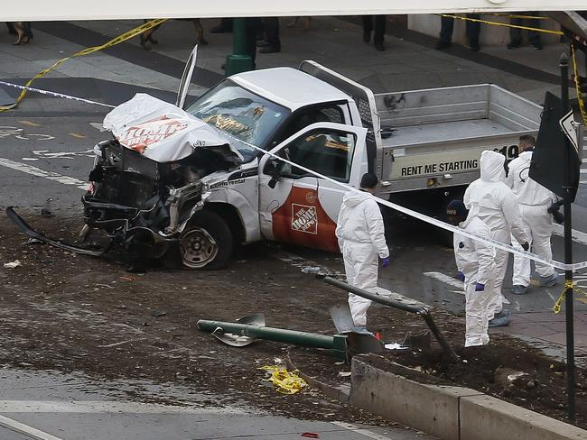 Authorities stand near the ute used to mow down cyclists and pedestrians. Picture: AP