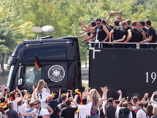 Germany's players brandish the World Cup trophy atop an open-deck bus and surrounded by fans.
