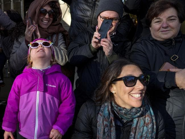 Adults and children along Central Park West watch a passing balloon during the Macy's Thanksgiving Day Parade in New York. Picture: AP