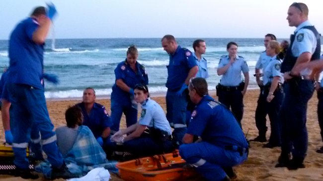 Paramedic treat the shark victim. It is believed to be the first shark attack at the beach in 14 years. Pictures: Ayn Mielke