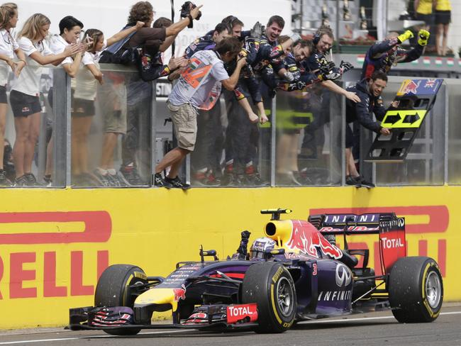 His team celebrates as Ricciardo crosses the line.