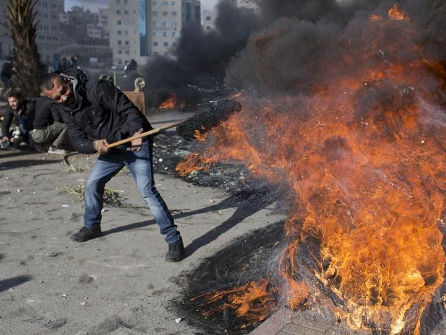 A Palestinian protester burns tires during clashes with Israeli troops following protests in the West Bank city of Ramallah. Picture: AP