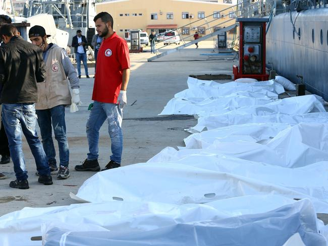 Libyan paramedics and aid workers stand next to the bodies of African migrants at a naval base in Tripoli. Picture: AFP