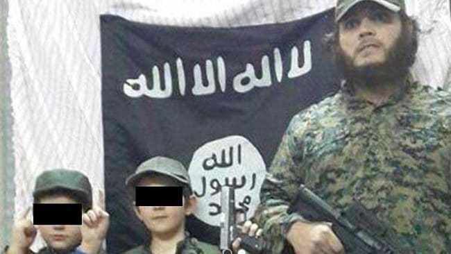 Australian Khaled Sharrouf and boys believed to be his three sons (one not visible) stand in front of the Islamic State flag in an image posted on Twitter. Source: Supplied